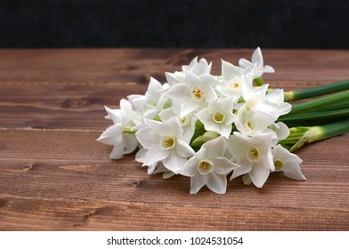Close-up of a freshly cut bunch of white narcissi, lying on a wooden table