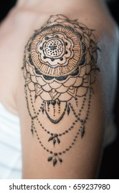 Closeup freshly done henna tattoo on woman's shoulder