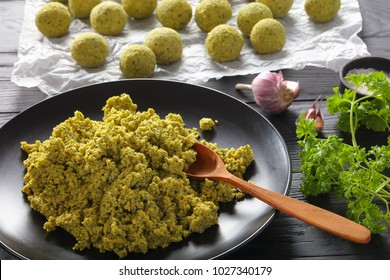 close-up of freshly ground chickpea mixed with greens and spices and raw falafel balls prepared to be fried or oven baked, authentic recipe, view from above