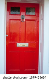 close-up of a freshly painted bright red front door with Lion head door knocker