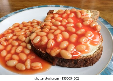 Close-up of freshly prepared, traditional Beans on Toast, in this case wholemeal bread. Ready to eat, the healthy snack can be seen on a wooden dinning table.