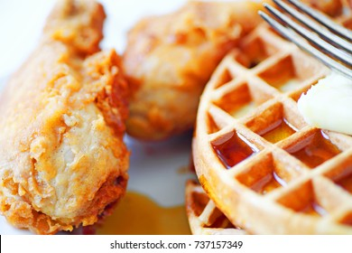 Closeup of fried chicken legs, Belgian waffles, butter and maple syrup with a fork
