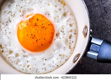 Close-up fried egg in fryin pan with salt and pepper.