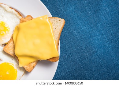 Closeup of fried eggs and toast cheese on a blue tablecloth. Tasty breakfast. Top view.