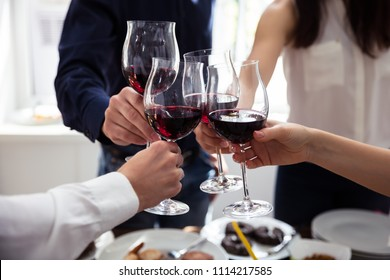 Close-up Of Friends Toasting Wineglasses At Party