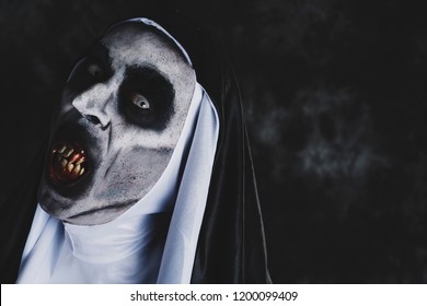 closeup of a frightening evil nun, with bloody teeth and scary eyes, wearing a typical black and white habit, against a dark background, with some blank space on the right