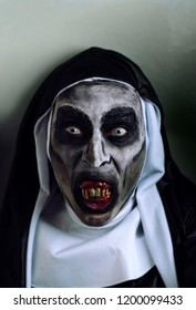 closeup of a frightening evil nun, with bloody teeth, wearing a typical black and white habit