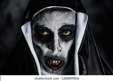 closeup of a frightening evil nun, with bloody teeth and scary eyes, wearing a typical black and white habit
