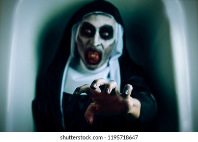 closeup of a frightening evil nun, wearing a typical black and white habit, with a threatening gesture, emerging from a white coffin