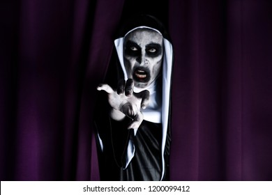 closeup of a frightening evil nun, wearing a typical black and white habit, peeping out from a purple curtain