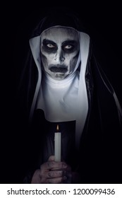 closeup of a frightening evil nun, wearing a typical black and white habit, against a black background, with a lit candle in her hands