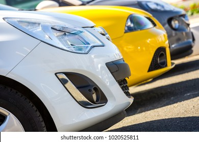 Closeup of front head light of blue car with other cars in showroom