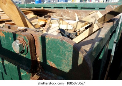 Closeup front part of heavy industrial skip. The big green bin is full of building material. Space to add text on blurred wood and rusty metal area in background. Great for rubbish recycle concept.