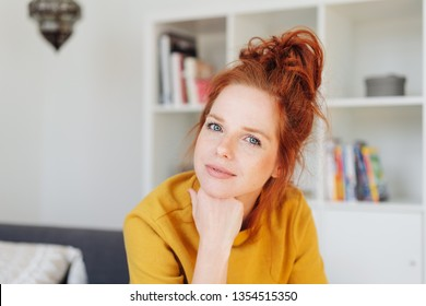 Close-up front portrait of beautiful young red-haired woman in yellow shirt, sitting in living room and friendly looking at camera, propping her chin with her fist