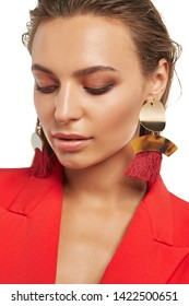 Closeup front shot of girl with tanned skin, wearing rich red blazer and long dangle earrings, decorated with massive metal pendants and red tassels. The woman with slicked down hair is looking down.