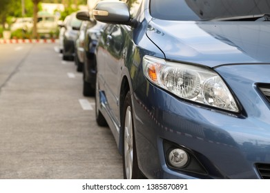 Closeup of front side of blue car parking in parking lot beside the street in sunny day with natural background. The normal way of transportation in the city.
