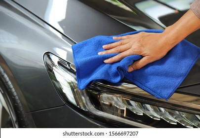 Closeup of front side of gray car cleaning  with blue microfiber cloth by woman owner's hand in sunny day. The simply family activity and lifestyle.