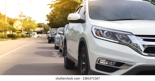 Closeup of front side of white car parking beside the street in sunny day with natural background. Normal way of transportation in modern world.