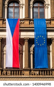 Closeup front view of a Czech flag next to a EU flag hanging on a balcony  on a old city building in Prague.
