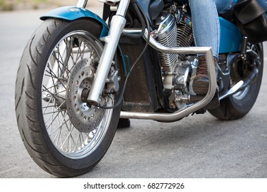 Close-up, front view at motorcyclist foot with protective brown boot on the stands of motorbike with chrome protective arcs