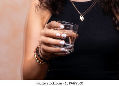 A closeup and front view on a young woman suffering from Parkinson's disease, the wrist and hand tremors whilst trying to drink, the disorder usually affects the elderly.