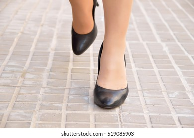 closeup front view of a young female walking along a street wearing stilettos on the city sidewalk