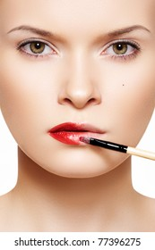 Close-up frontal portrait of beautiful woman model applying lipstick using lip concealer brush
