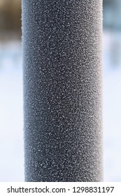 A closeup of a frozen silver colored metal pipe. Photographed during a cold winter day in Finland. You can see the beautiful texture made by the frost crystals and snow flakes. Lovely texture!