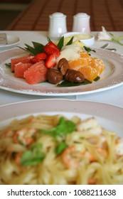 Close-up of fruit salad dessert with big shrimp pasta