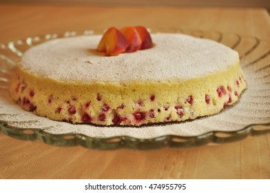 A close-up of a fruit sponge cake on a serving plate