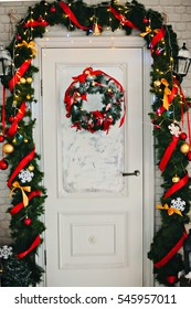Close-up of fruit themed Christmas wreath on a pale green door.