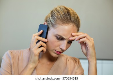 Close-up of frustrated young woman talking on phone