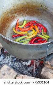 Closeup of frying red and green chilies in big pot on open fire
