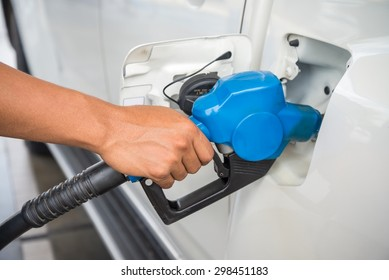 Closeup fueling blue fuel nozzle Car into Gas Tank