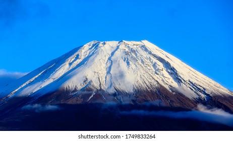 Closeup Fuji mountain Fujisan beautiful snowcapped volcano and blue sky background in japan
