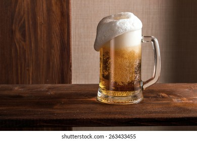 close-up of a full glass of beer on wood background