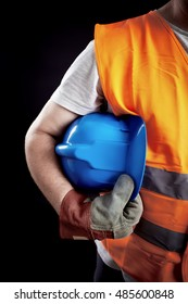Close-up of a full protective gear (protective gloves, orange reflective vest, blue hardhat). Concept image.