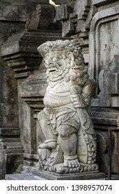 Closeup of a full size stone carved statue depicting half profile of warrior god in  Balinese Hindu holy spring temple Tirta Empul (Tampaksiring, Bali,  Indonesia)