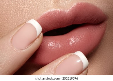 Close-up of full woman's lips with natural light makeup. Beauty macro sexy female mouth  and french manicure on nails. Naturel tender look