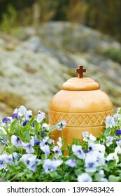 closeup of funerary urn surrounded by blue violets ready for spreading of the ashes in the woods