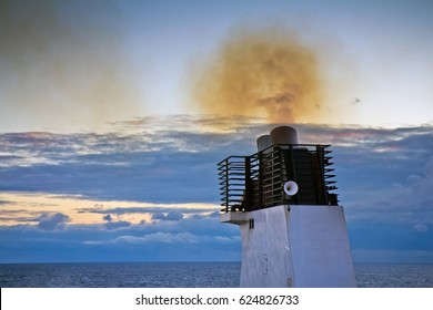 Closeup of funnel of a cargo ship floating in the Baltic sea with smoke polluting environment against cloudy sky in the evening