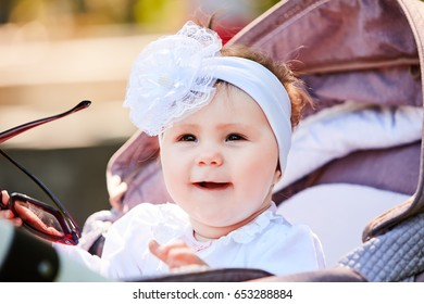 Close-up of the funny baby girl sitting in the stroller and holds sunglasses.