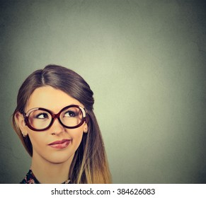 Closeup funny confused skeptical woman in glasses thinking planning looking up isolated on gray wall background copy space above head. Human face expression emotion feeling body language, perception