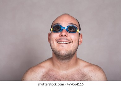 Closeup of funny naked man in swimming goggles daydreaming and looking up.