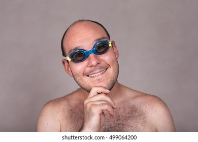 Closeup of funny naked man in swimming goggles daydreaming and looking at you.