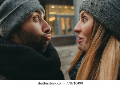Close-up of a funny portrait of a loving and happy couple. The young guy and girl are fooling around and croaking their faces. Sensual photo