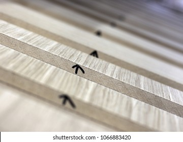Closeup of furniture details drying in carpenters workshop. Upper side marked by arrow. Shallow DOF.