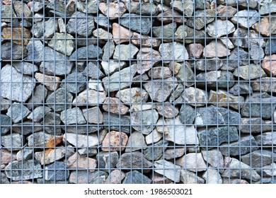 Nahaufnahme des Gabion-Zauns. mit verschiedenen Kalksteinarten gefüllt