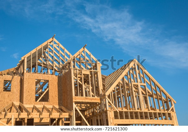 Close-up of gables roof on stick built home under construction and blue sky in Humble, Texas, USA. New build roof with wooden truss, post and beam framework. Timber frame house, real estate background