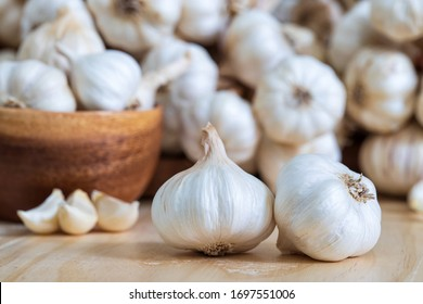 Closeup of Garlic bulbs on wooden table with garlics blur background.